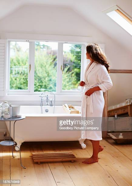 Woman in robe getting ready to take bath at spa