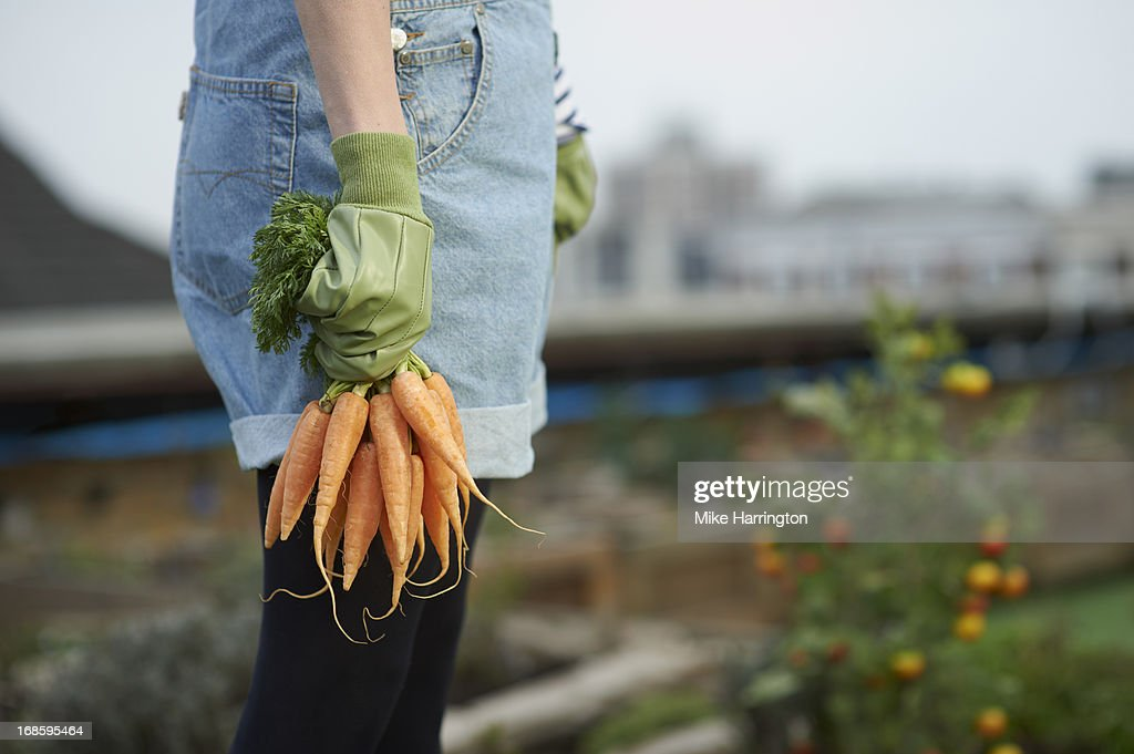 Woman in roof garden holding carrots.