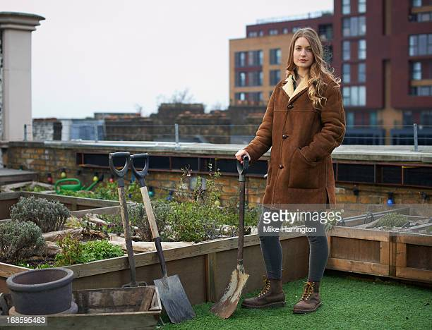 Woman in roof garden in urban location with spade.