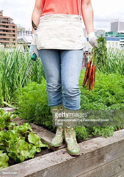 woman in rubber boots holding carrots in one hand