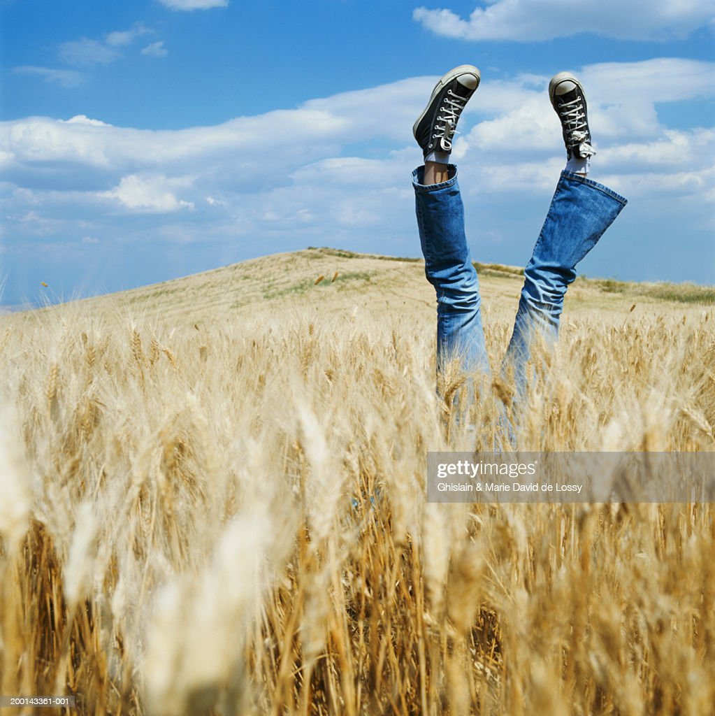 Woman in rural landscape, legs in air, low section
