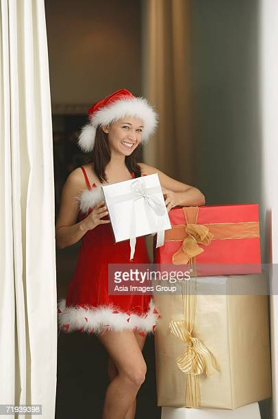 Woman in Santa hat and red dress holding gift box, smiling at camera