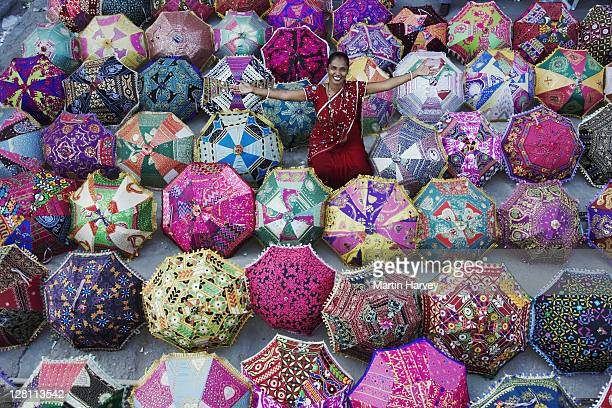 Woman in sari amongst colorful umbrellas outside a shop. Jaipur, India. (MR) (PR: Property Released)