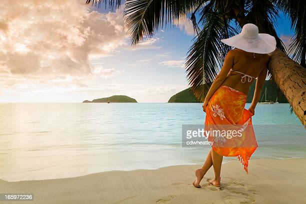 Mujer en el sombrero sarong y disfrutar de la vista al mar Caribe