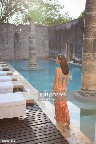 Woman in sarong walking by resort swimming pool