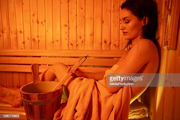 Woman in Sauna with Water Bucket