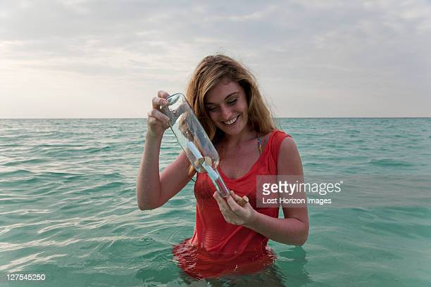 Frau im Meer mit message in a bottle