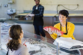 Woman in seafood market helping customer
