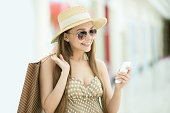 Portrait of young pretty happy smiling sexy woman wearing hat and sunglasses standing in shopping center, holding shopping bag and mobile phone, using smartphone app, looking at screen, messaging
