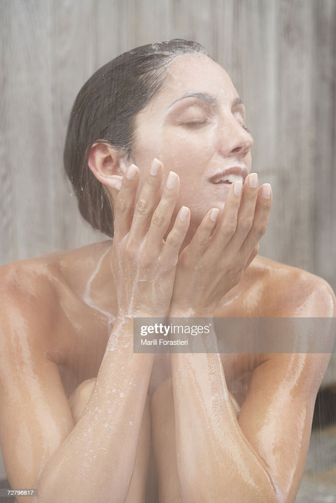 Woman in shower, shampoo running down face and body : Stock Photo