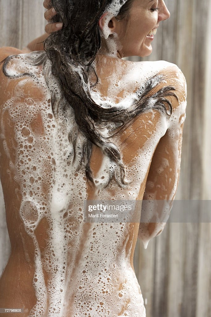 Woman in shower, smiling, soap bubbles, rear view : Stock Photo