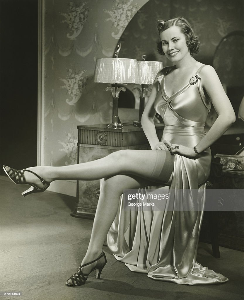 Woman in silk evening gown sitting by vanity table, showing leg, (B&W) : Stock Photo