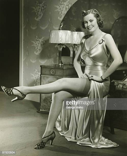 Woman in silk evening gown sitting by vanity table, showing leg, (B&W)