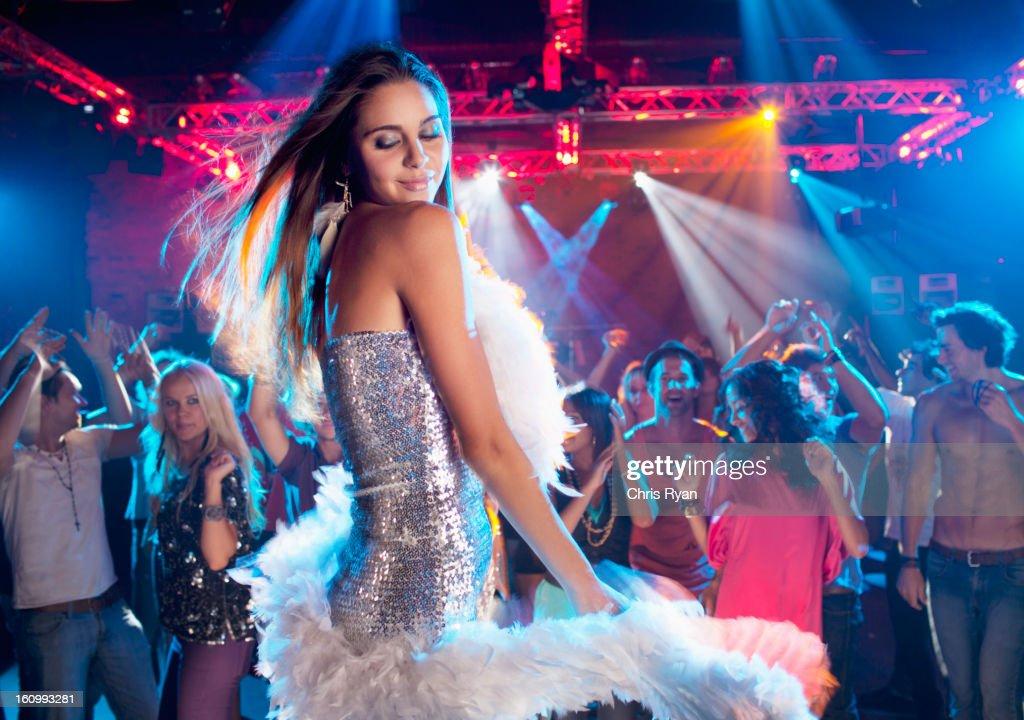 Woman in silver dress with feather boa dancing in nightclub