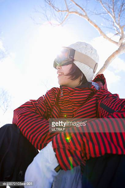 Woman in ski goggles sitting outdoors