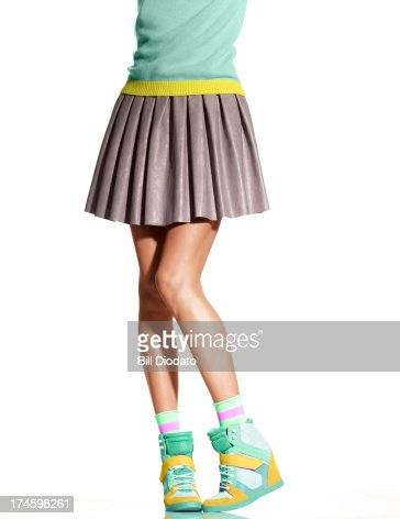 Woman in skirt and wedge sneakers