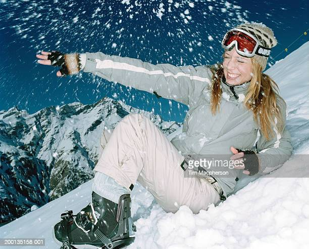 Woman in skiwear laughing, sitting on slope in flurry of snow