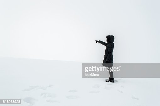 Woman in snow pointing her finger towards blank space : Stock Photo