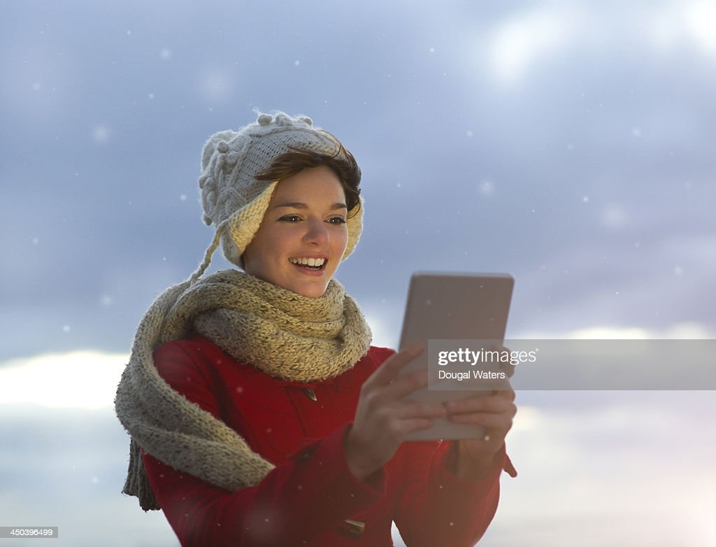 Woman in snow using digital tablet at Christmas. : Stock Photo