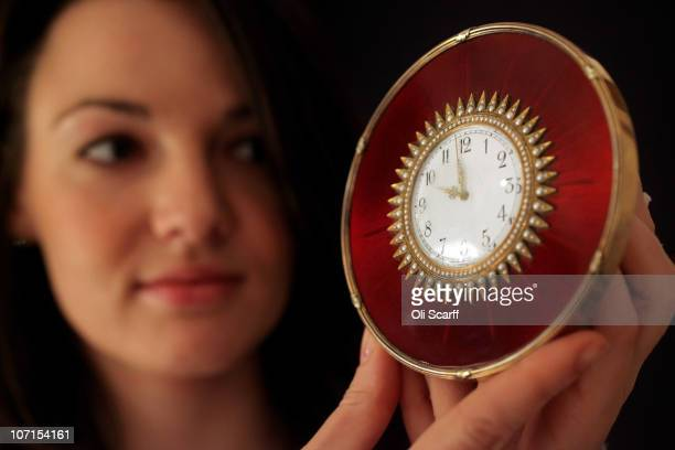 Woman in Sotheby's auction house examines a Faberge enamel silvergilt and seed pearl clock made around 1908 which features in a forthcoming auction...