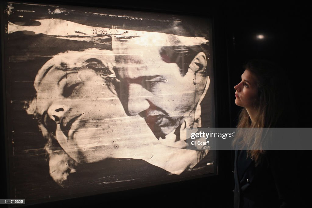 A woman in Sotheby's auction house views an artwork by Andy Warhol entitled 'The Kiss' which is expected to fetch 900,000 GBP on May 18, 2012 in London, England. The artwork features in Sotheby's forthcoming sale from the collection of Gunter Sachs which is to be held on May 22 and 23, 2012 in London. The collection of over 300 works owned by the late husband of Brigitte Bardot is expected to fetch in excess of 20 million GBP.