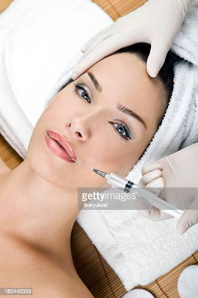 Woman in spa environment receiving facial injection