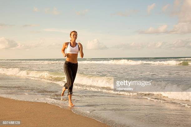 woman in sport outfit running along beach shoreline in Florida