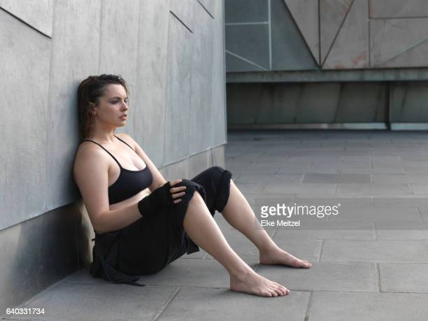 woman in sport outfit sitting on the ground