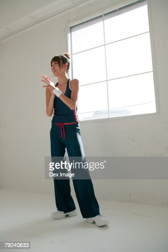 Woman in sports attire standing in front of window : Stock Photo