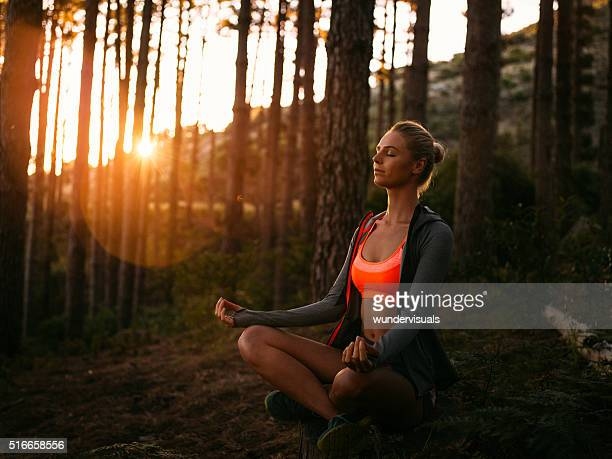 Woman in sports clothing meditating in a forest at sunrise