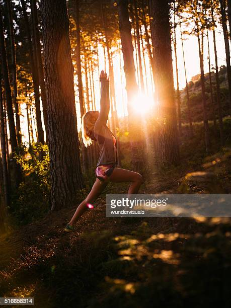 Femme en vêtements de sport performance du Yoga dans la forêt le matin