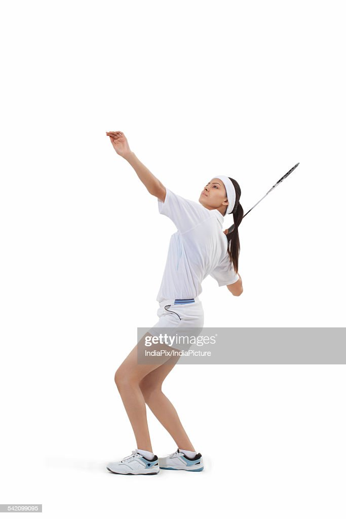 Woman in sports wear playing badminton against white background