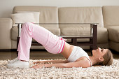 Joyful attractive young woman lying on floor in living room and doing hip bridge exercise. Happy smiling lady in sportswear lifting pelvis on carpet, enjoying physical activity and fitness at home