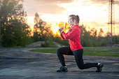 Fit woman in sportswear doing frontal lunges (squats). Fitness, workout, sport outdoors concept.