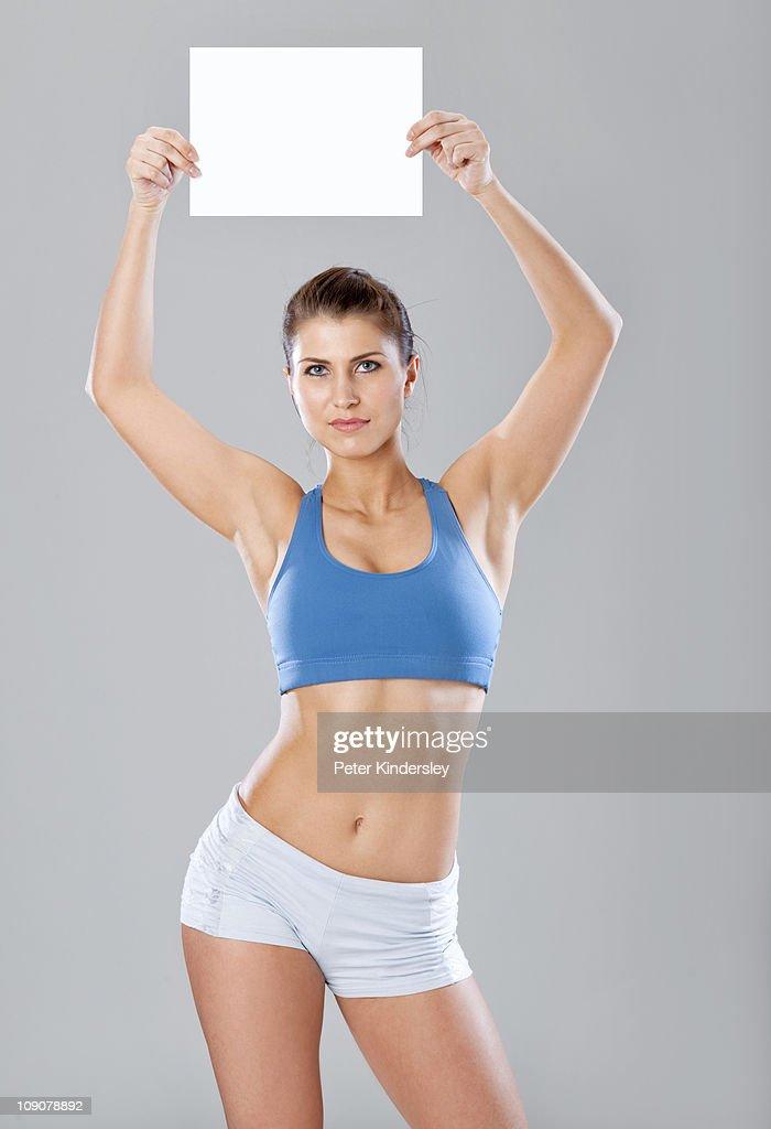 Woman in sportswear holding blank message : Stock Photo