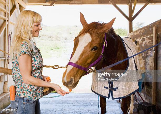 Woman in stable feeding horse