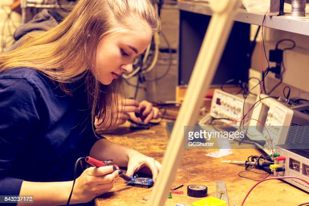 Woman in STEM working seriously on her electronics project