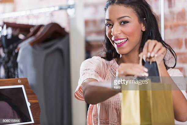 Donna nel negozio con shopping bag sul banco di check-out