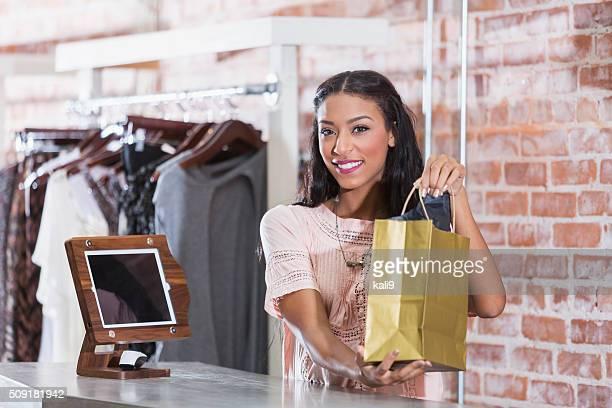 Mujer en tienda sostiene bolsa de la compra en el momento de la compra, contador