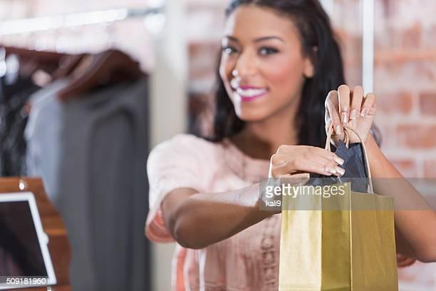 Donna nel negozio con shopping bag sul banco di check-out