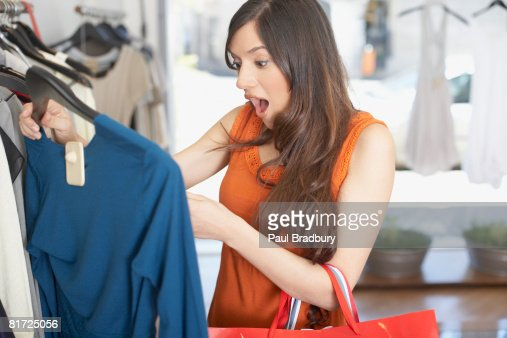 Woman in store looking at a shirt in shock : Foto de stock