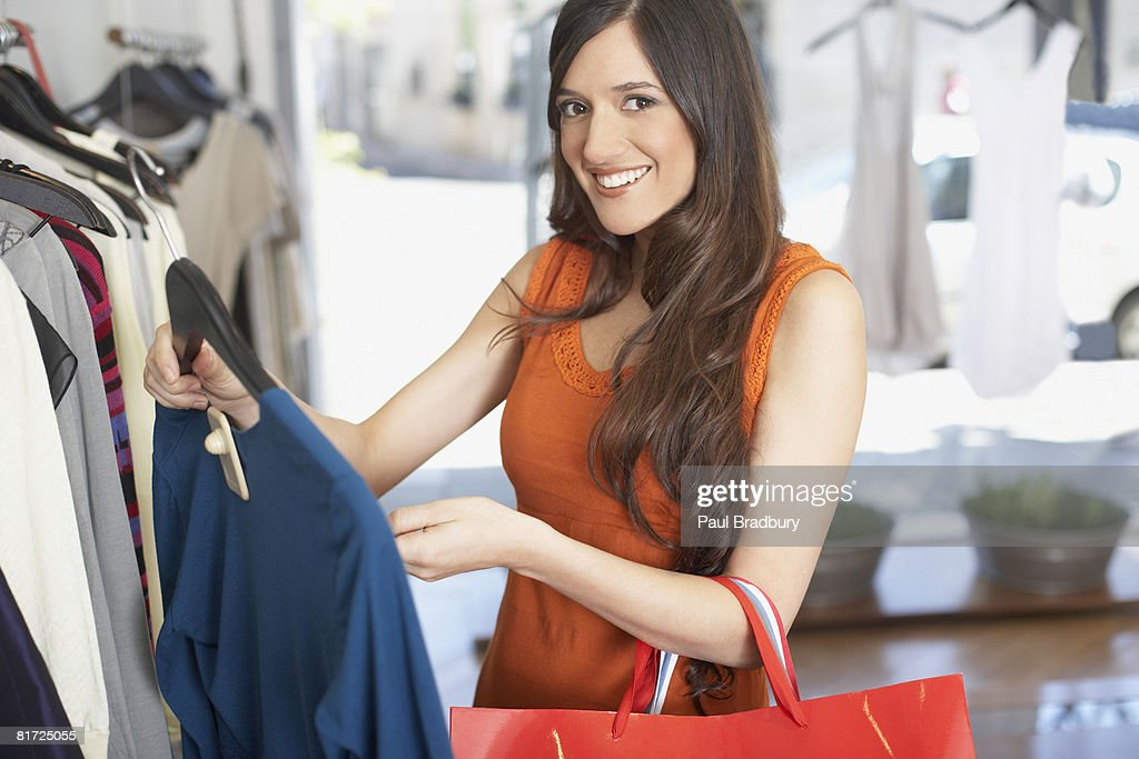 Woman in store looking at a shirt smiling : Stock Photo