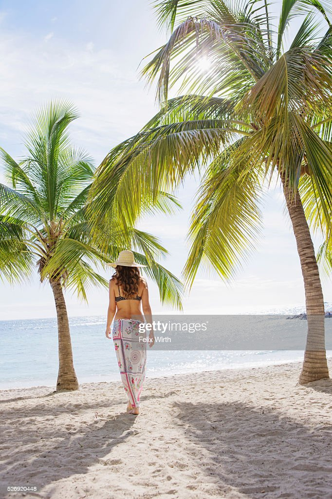 Woman in straw hat walking towards sea : Stock Photo