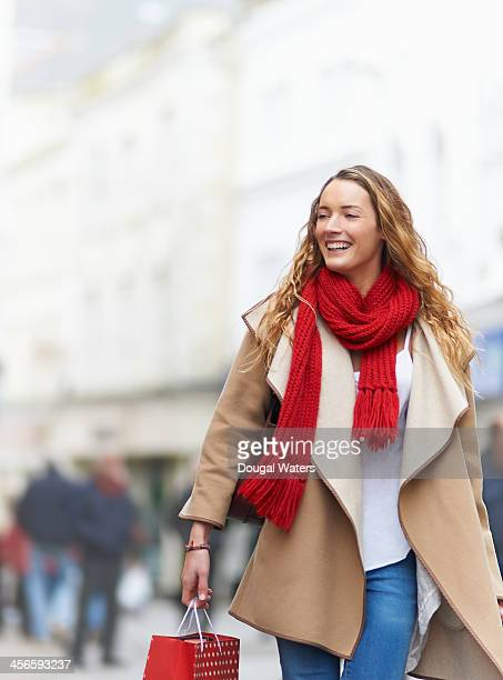 Woman in street carrying Christmas shopping.