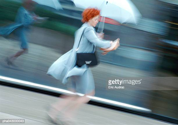 Woman in street holding umbrella, blurred