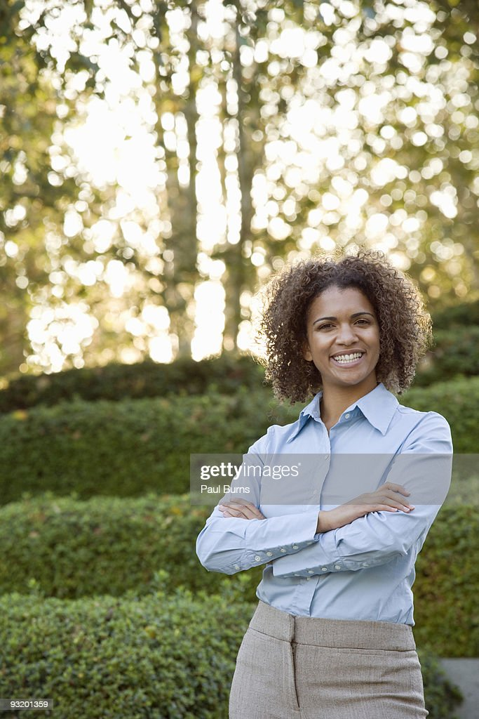Woman in suit smiling and crossing arms in garden : Stock Photo