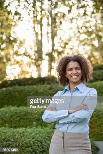 Woman in suit smiling and crossing arms in garden : Bildbanksbilder