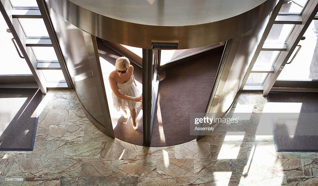 Woman in sun dress walks into hotel lobby. : Stock Photo