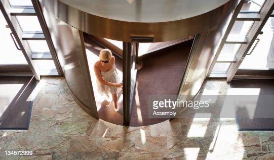 Woman in sun dress walks into hotel lobby.