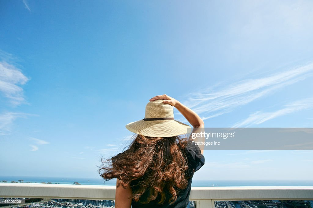 Woman in sun hat admiring scenic view from balcony